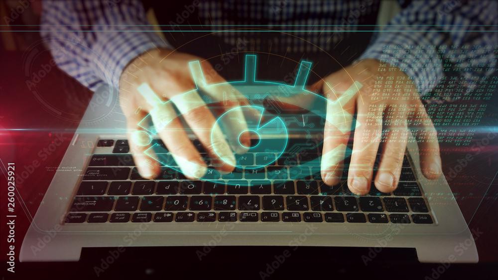 Fototapeta Man writing on laptop keyboard with spy eye