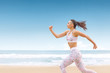 Young athlete woman jogging on the sea beach