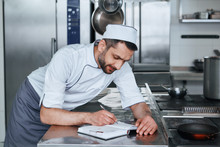 Focus On Food Safety. Happy Chef Cook Standing In Commerical Kitchen