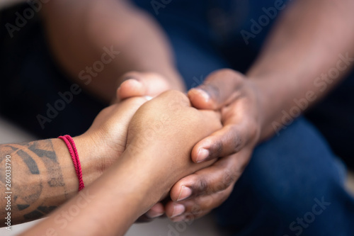 Fotografering  Black man friend holding hands of african woman, closeup view