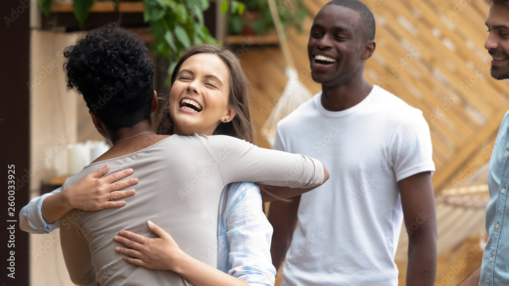 Fototapety, obrazy: Happy caucasian teen girl embracing african friend at group meeting