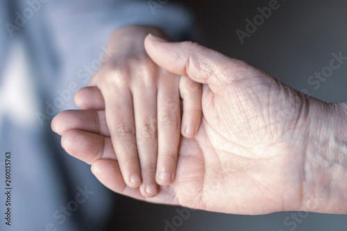 mano de mujer mayor sujetando mano de niña Wallpaper Mural