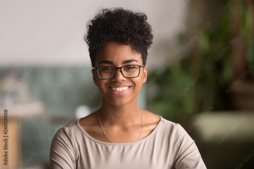 Fototapeta Headshot portrait of happy mixed race african girl wearing glasses