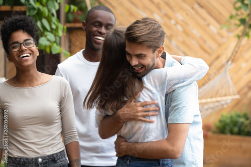 Valokuva Happy man and woman greeting hugging at multi-ethnic friends meeting
