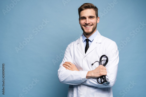 Fototapeta Portrait of confident young medical doctor on blue background. obraz
