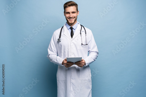 Fotografia  Portrait of confident young medical doctor on blue background.