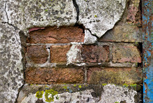 Flaking And Cracked Render Revealing Brickwork On Condemned Derelict Factory Building Awaiting Demolition