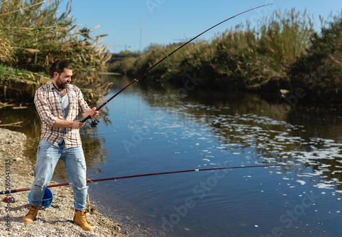 Canvas Prints Fishing Adult man standing near river and pulling fish expressing emotions of dedication