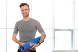 Fototapeta Łazienka - Content confident handsome male yoga instructor with exercise mat standing against window and smiling at camera