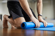 Leinwanddruck Bild - Close-up of unrecognizable man standing on knees and rolling out exercise mat after yoga training in gym