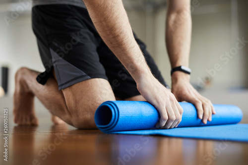Obraz Close-up of unrecognizable man standing on knees and rolling out exercise mat after yoga training in gym  - fototapety do salonu