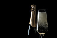 Bottle And Glass Of Champagne On Black Background, Space For Text