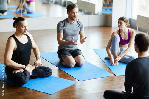 Photo  Serious handsome young man in gray tshirt sitting on knees in yoga classroom and