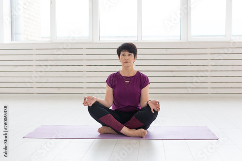 Fotografie, Obraz  Sport, yoga, people concept - Sporty middle-aged woman practicing yoga indoors
