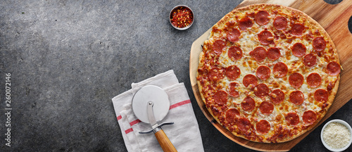 Photo sur Aluminium Pizzeria pepperoni pizza on wooden serving board shot top down with copy space composition