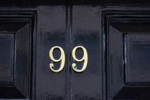 House Number 99 With The Ninety-nine In Bronze On A Black Painted Wooden Door