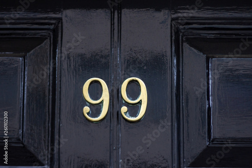 House number 99 with the ninety-nine in bronze on a black painted wooden door Poster Mural XXL