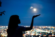 Silhouette Woman Portrait With Full Moon In City Night Light Bokeh Background , Chiang Mai ,Thailand