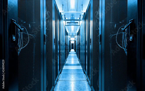 Fotografia, Obraz  Dark blue data centre interior with rows of hardware equipment