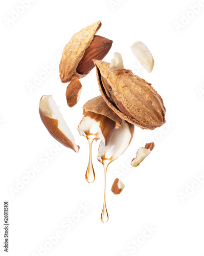 Photo Drops of oil dripping from almond close-up on a white background