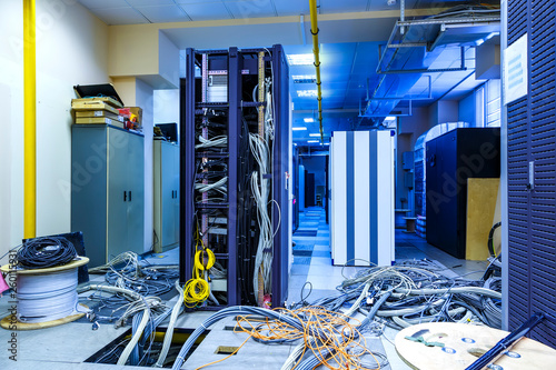 Valokuva  Server room with racks in datacenter and internet problem causing by disorder of wiring