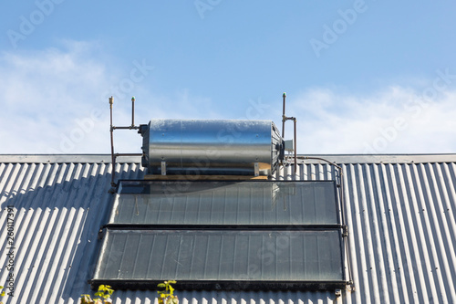 Fototapeta Rooftop solar hot water cylinder with photovoltaic cells  on domestic house conv