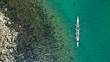 Aerial drone bird's eye view of sport canoe operated by team of young women in tropical caribbean exotic island with emerald and sapphire clear sea