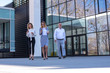 Group of business people walking outdoor in front of an office building