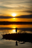 Silhouette of woman taking photo of sunset with mobile phone, reflection in water. - 260129782