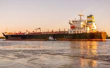 A Big Ship Is Traveling At Mississippi River Under Sunset