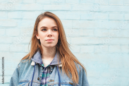 Fotografie, Obraz  Attractive girl with a serious face standing against the background of a blue wall and looking away, wearing a blue jeans jacket