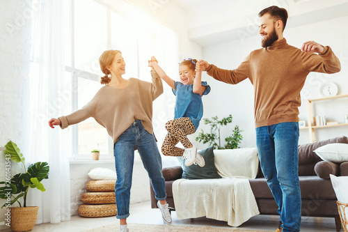 Poster Hoogte schaal happy family mother father and child daughter dancing at home