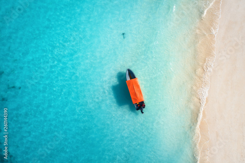 Foto auf Gartenposter Sansibar Aerial view of the fishing boat in clear blue water at sunny day in summer. Top view from drone of boat, sandy beach. Indian ocean. Travel in Zanzibar, Africa. Landscape with motorboat, sea. Seascape