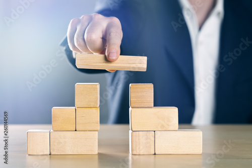 Business man bridging the gap between two towers or parties made from wooden blo Fotobehang