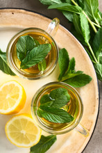 Freshly Prepared Mint Herbal Tea In Glasses, Garnished With Mint Leaves, Photographed Overhead (Selective Focus, Focus On The Leaves On The Tea)