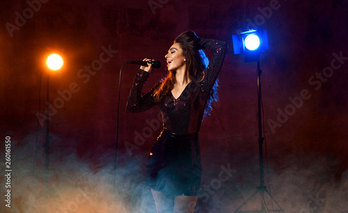 Beautiful singing girl curly afro hair singer sing with microphone karaoke song on stage on dark neon light - 260161550