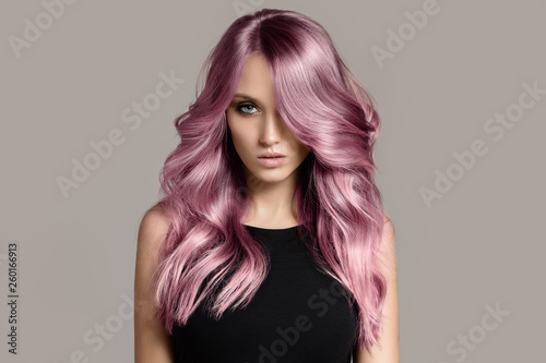 Beautiful woman with long wavy coloring hair. Flat gray background. - fototapety na wymiar
