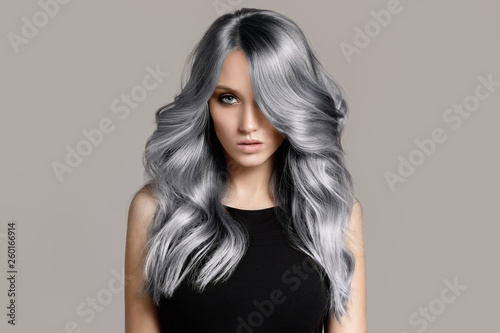 Obraz Beautiful woman with long wavy coloring hair. Flat gray background. - fototapety do salonu