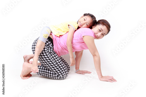 Portrait of a happy daughter piggyback ride her mother, isolated over white Wallpaper Mural