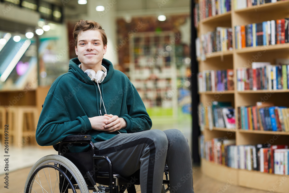 Fototapety, obrazy: Content handsome young disabled student with headphones on neck siting in wheelchair and looking at camera in modern library or bookstore