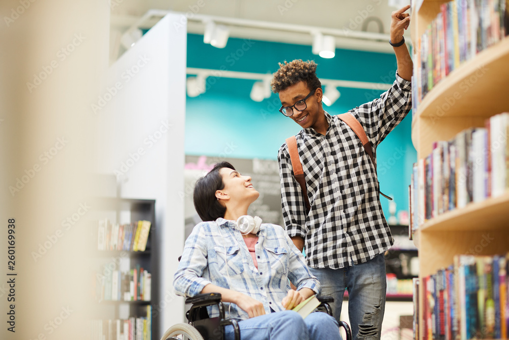 Fototapety, obrazy: Cheerful handsome black guy with Afro hairstyle helping disabled student girl to take book from shelf in library