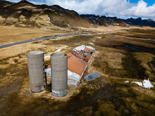 Two Old Abandoned Silos By A Decaying Barn With Mountain Landscapes Behind It
