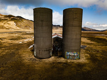 Old Abandoned Silos By A Decaying Barn With Mountain Landscapes Behind It