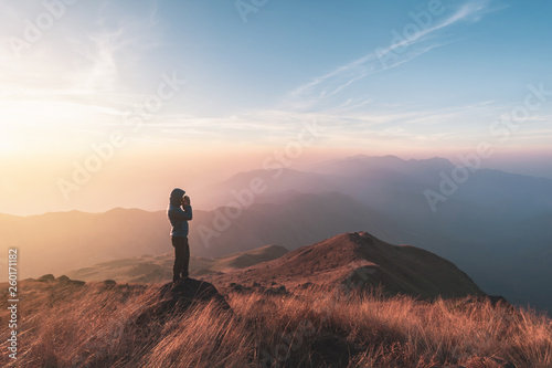 Fototapeta  Young man traveler looking beautiful landscape at sunset on mountain, Adventure