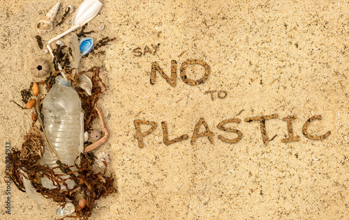 Fotografia Real plastic bottle, with cap and plastic straw washed up on beach mixed with seaweed shells and feathers