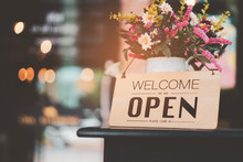 Open Sign Front Of Cafe Shop With Flower And Bokeh Light Abstract Background.