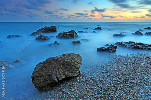 Poster Turquoise Beautiful seascape with sunset on the rocky shore of a tropical beach and Island