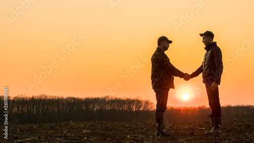 Fotografia Two farmers on the field shake hands at sunset