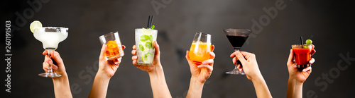Hands holding classic cocktails on rustic background