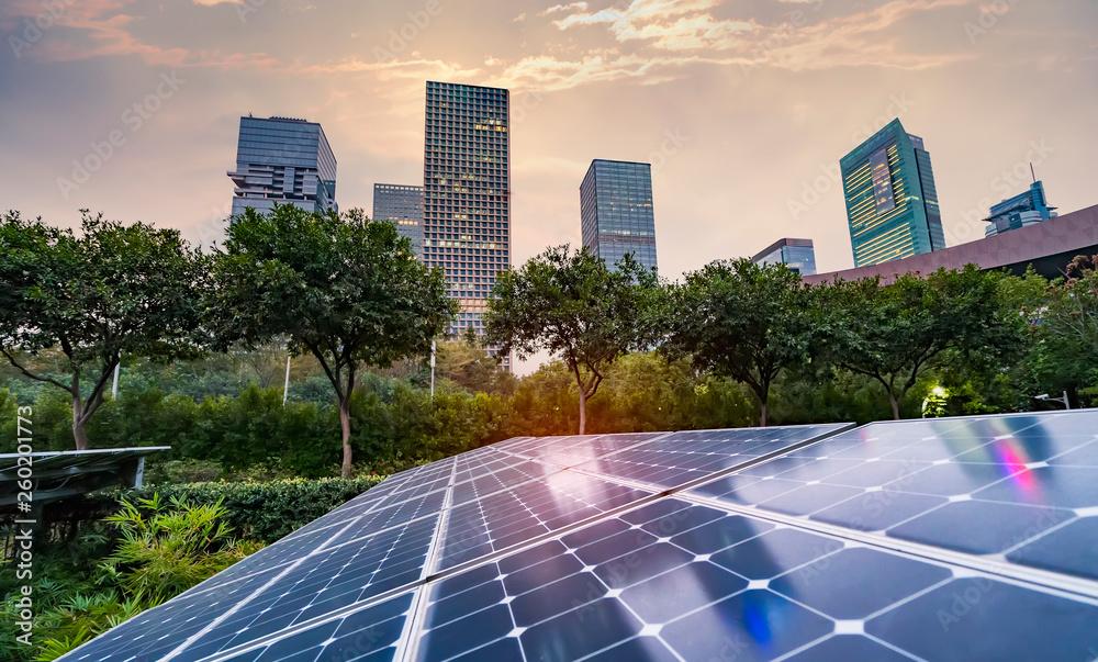 Fototapeta Ecological energy renewable solar panel plant with urban landscape landmarks